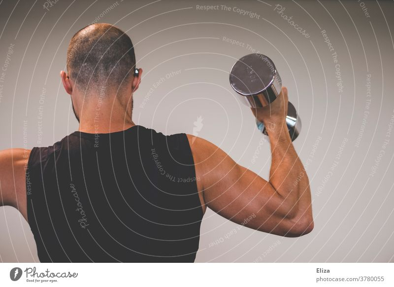 A muscular man with trained biceps lifts a 10 kilo dumbbell. Man Dumbbell chiselling Muscular Sports weight training Force Upper arm Biceps Strong Body Fitness
