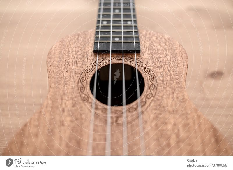 Brown ukulele on wooden background with shallow depht of field instrument acoustic musical string brown guitar rosette hawaiian object art closeup close up