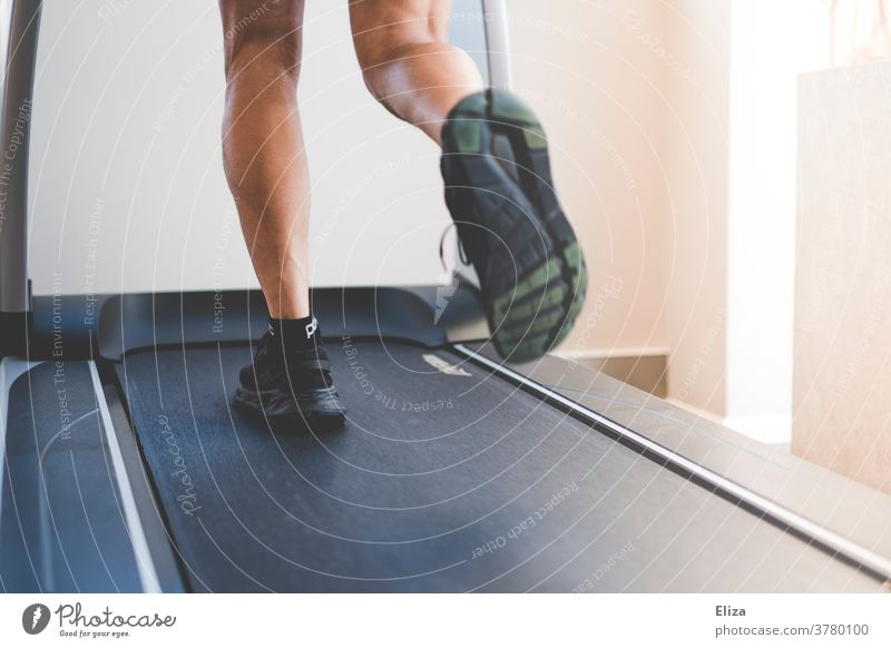 A man runs on a treadmill in the gym. Detail of the legs in motion. Moving pavement Walking Jogging Fitness centre Sports workout Athletic Fitness studio Legs
