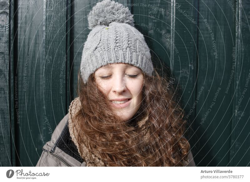 portrait of a girl with closed eyes, long hair and a gray cap leaning against a green wooden door isolated white smile caucasian studio lady face childhood cute