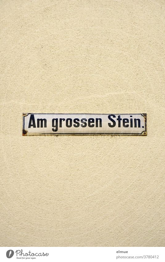"""Street sign """"Am großen Stein"""" on a beige house wall At the big stone street name street sign Wall (building) Facade writing Signage address dwell Old bailer"""