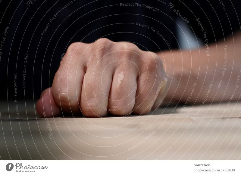 A clenched fist on a table. Anger, aggression. Fist by hand Table furious Aggression Force Aggravation sensation Fingers Woman Hatred arm Impatience nervous