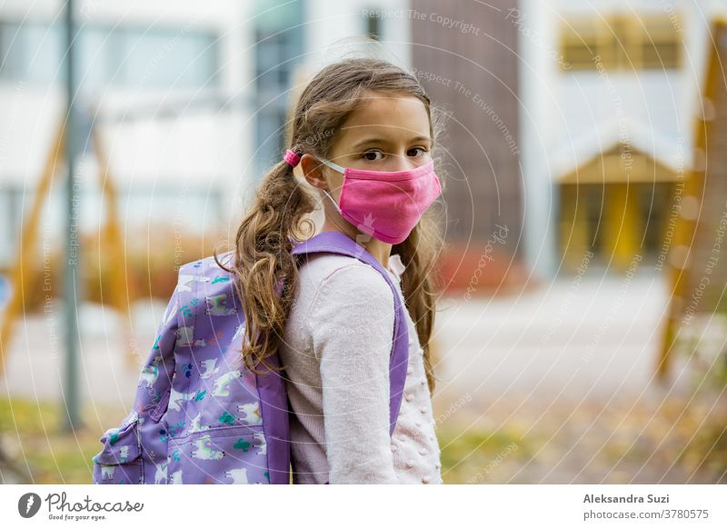 Schoolgirl wearing protective fabric reusable face mask going to school. School education during the coronavirus pandemic. Security measures and social distancing