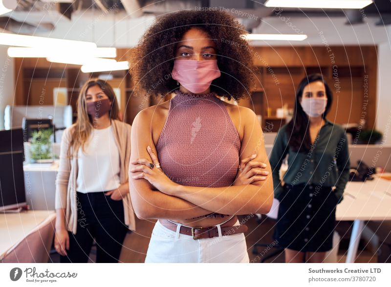 Portrait Of Female Business Team Wearing Face Masks In Open Plan Office During Covid-19 Pandemic business businesswomen team face mask face covering ppe office