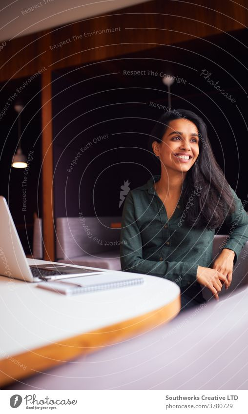 Businesswoman Sitting At Meeting Table Working On Laptop In Modern Open Plan Office business businesswomen meeting office sitting boardroom table laptop