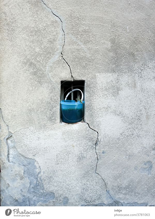old bucket in front of small window in old facade with crack Colour photo Bucket Blue Crack & Rip & Tear Facade Copy Space Middle Gloomy Diagonal Plaster Gray
