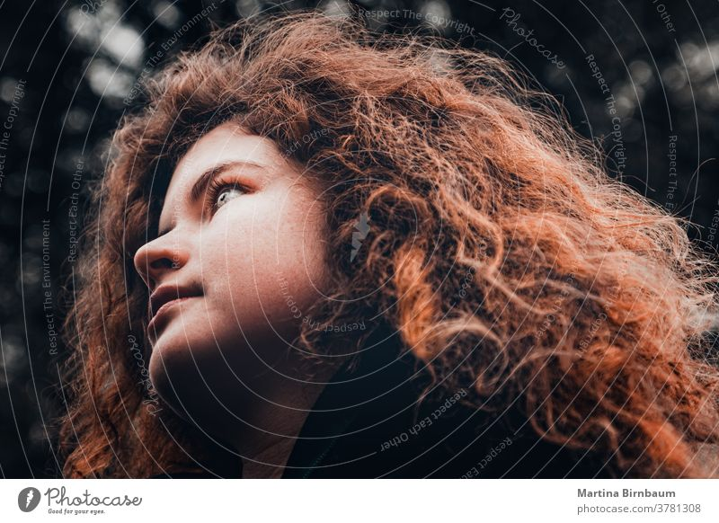 Young woman with wild red curly hair looking hopefully in the distance face girl one beautiful caucasian beauty person square hairstyle curls people vogue
