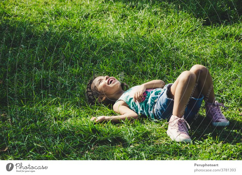 Little girl rests on the grass smiling on a sunny day child lying nature green smile spring kid kids relax field children meadow person flower summer fun young