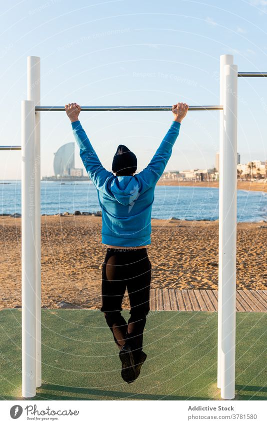 Strong man exercising on bar near sea training pull up beach workout fitness exercise sporty ocean active male healthy strong sports ground effort equipment