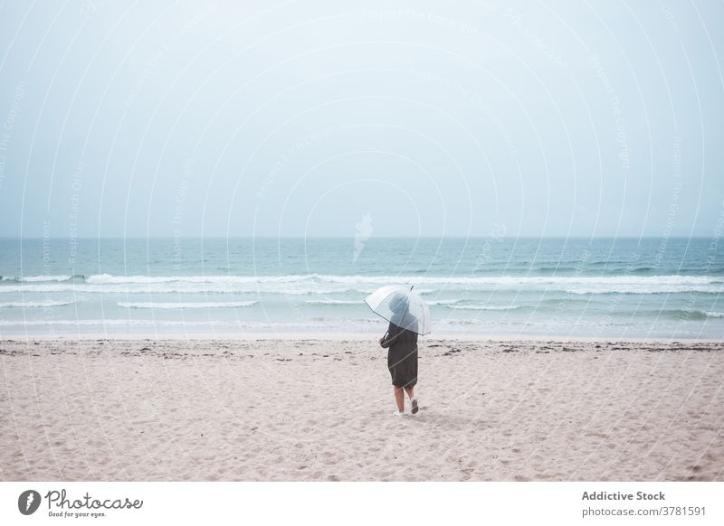 Anonymous person with umbrella walking on sandy beach sea alone travel ocean lonely stormy overcast traveler shore coast nature wave weather tourism seaside