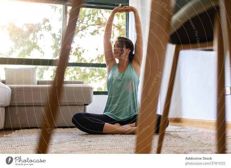 Serene woman doing yoga on floor at home practice flexible lotus pose legs crossed padmasana stretch female peaceful sportswear wellness carpet room harmony