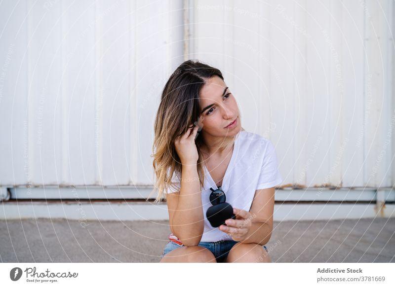 Young woman putting on earbuds on street put on adjust wireless earphones tws true wireless gadget device listen activity young female modern millennial