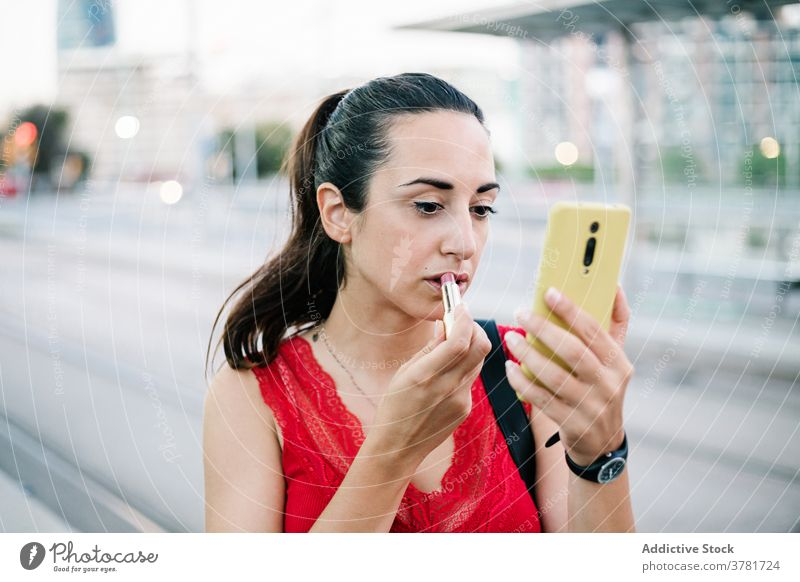 Young woman with smartphone applying lipstick on street makeup beauty cosmetic mobile urban modern cellphone device gadget young female brunette glamour style