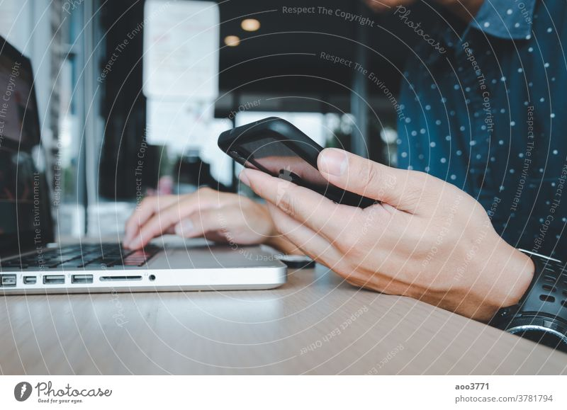 Man holding a cell phone and a laptop at a desk mobile table technology internet smartphone business computer people communication man hand digital work using
