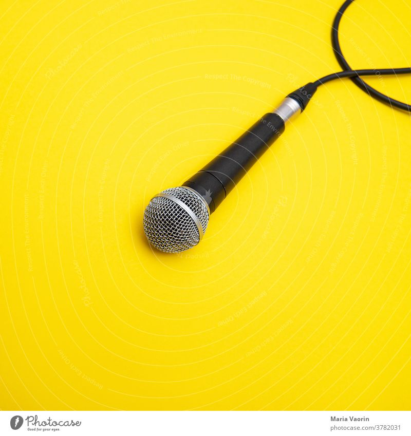 Mic Drop Microphone micro Music Concert String Hand microphone Yellow colored background Copy Space Rock music Podcast recording take