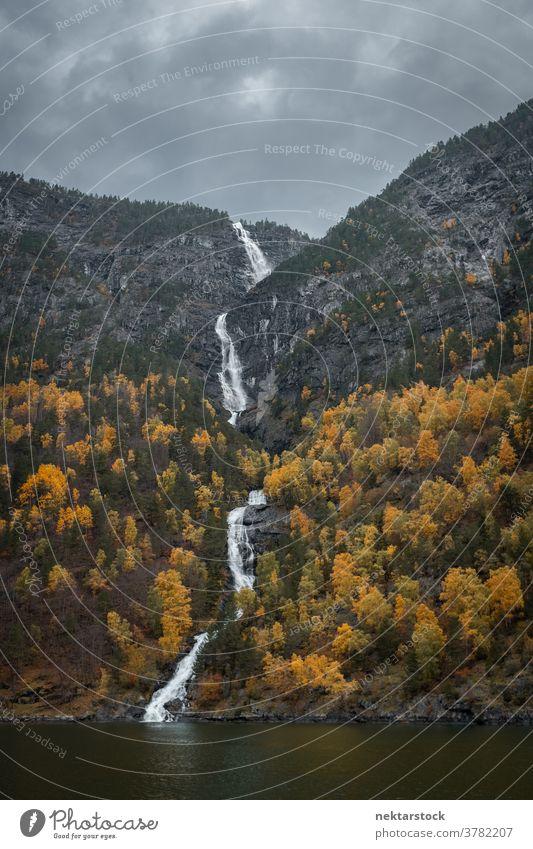 Kjosfossen Waterfall Flowing Between Autumnal Trees waterfall mountain autumn Norway north nature natural lighting outdoors scenery scenics landscape