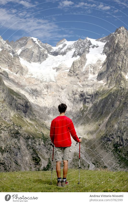 contempaltion and meditation concept: unrecognizable teenager look at a wonderful mountain landscape contemplation glacier hiking hiker male caucasian boy alone
