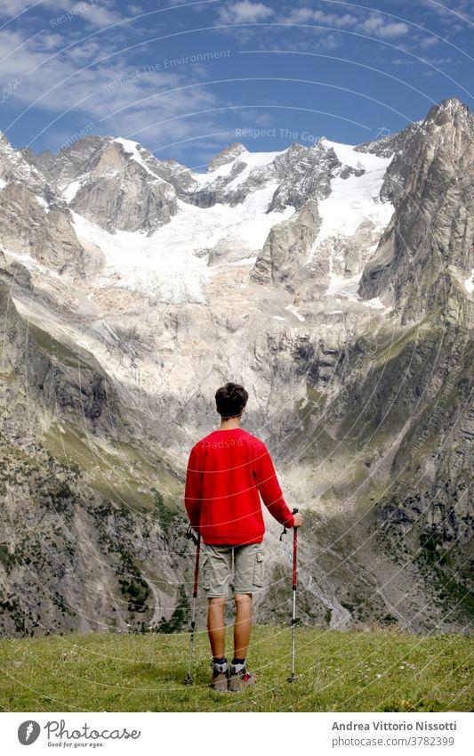 contempaltion and meditation concept: unrecognizable teenager look at a wonderful mountain landscape contemplation glacier hiking hiker male caucasian boy alone