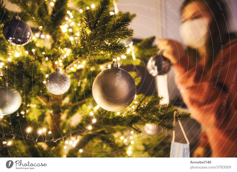 Young woman decorating a Christmas tree with medical safety mask for Covid-19, Coronavirus and Christmas concept, beautiful holiday new year home prevention