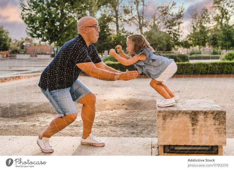 Man playing with girl in park in summer father daughter having fun together playful jump catch entertain city kid child bonding parent cheerful joy stone