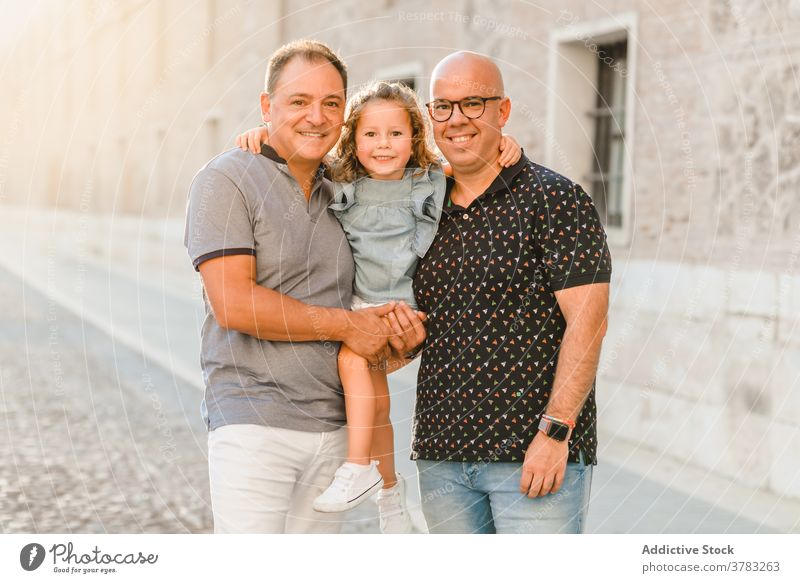 Delighted LGBT family walking on street lgbt together father men gay couple child entertain city passage weekend summer kid happy joy cheerful cute girl