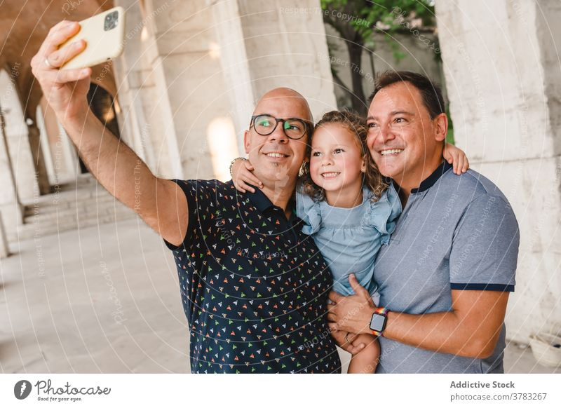 Cheerful LGBT family taking selfie in city lgbt child couple gay men girl smartphone homosexual together take photo self portrait cute daughter street smile