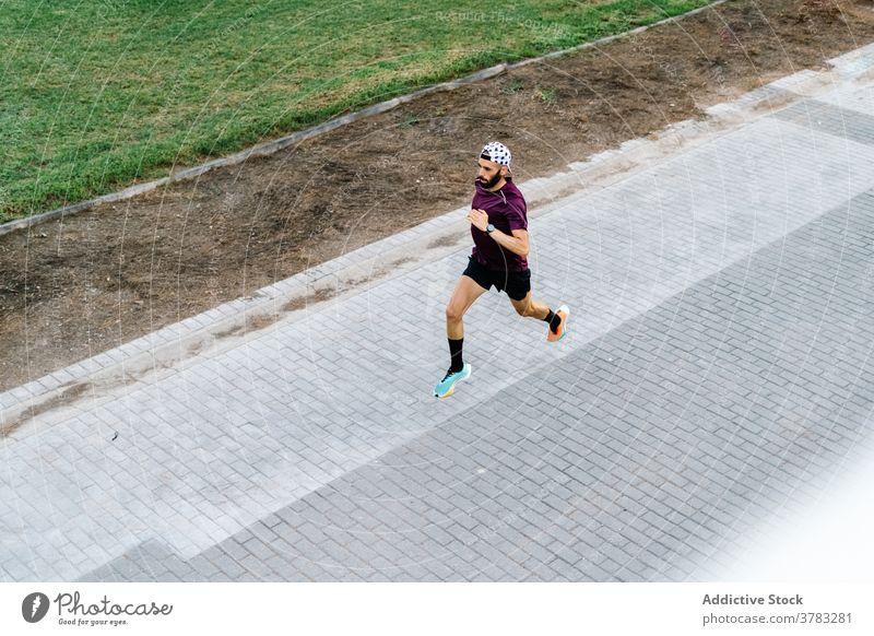 Male athlete running in asphalt road in park runner training man cardio sportsman summer activity male urban hill activewear fitness exercise sportswear jog