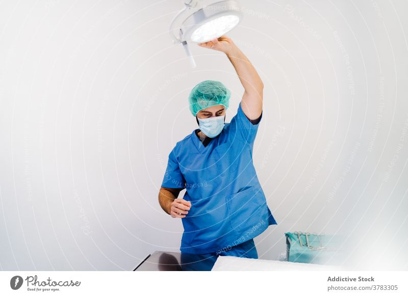 Male veterinarian preparing the lamp for surgery in clinic veterinary operating theater doctor prepare man machine table male uniform mask specialist work job