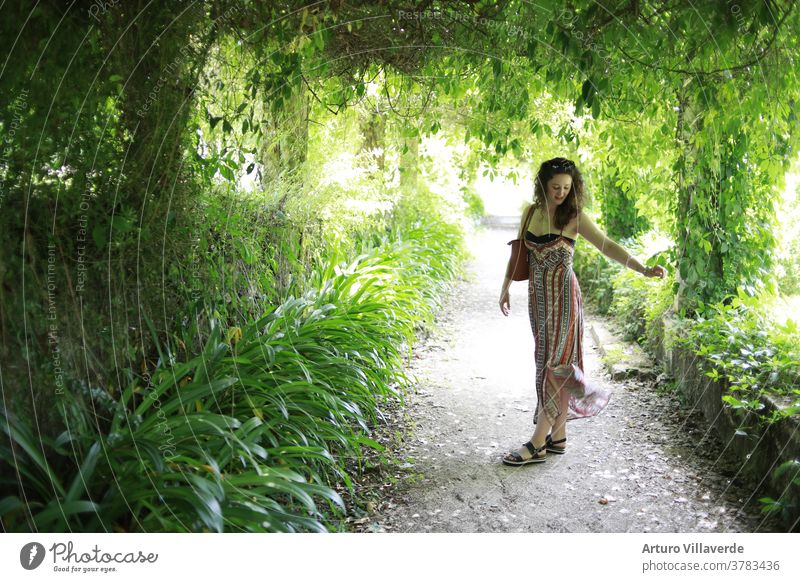portrait of a girl in a long dress surrounded by plants hair female posing luxury lady healthy multicolored colour stylish clothes vogue sexy sensual park
