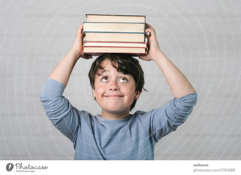 happy child with books on head education wisdom back to school kid childhood intelligence know learn study student think genius schoolboy smile lifestyle