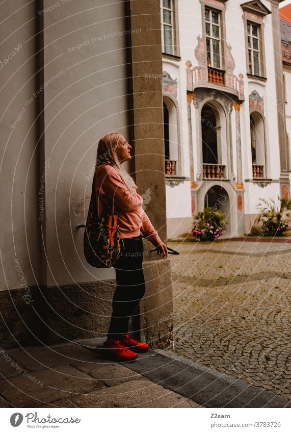Young woman stands in front of the castle Füssen Sightseeing feet Bavaria Athletic back view Blonde long hairs fashionable traditon Lock Entrance Museum Culture