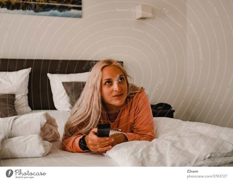 Young woman lies on the bed and zaps through the TV programs Television Remote control Blonde long hairs Bed relaxation Relaxation fortunate cheerful kind