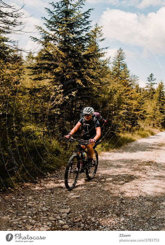 Young woman riding a MTB on a forest path Mountain bike mtb Bicycle Adventure stones Forest Alps mountains Nature Landscape Lonely Athletic Sports Backpack