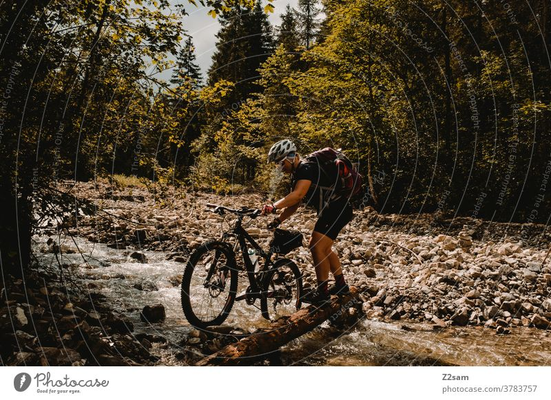 Young woman crosses river creek with her mountain bike Mountain bike mtb Bicycle Adventure Brook River Traverse Push stones Forest Alps mountains Nature
