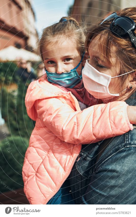 Family mother and her daughter standing in a street downtown wearing the face masks to avoid virus infection call care caucasian chat contagious corona