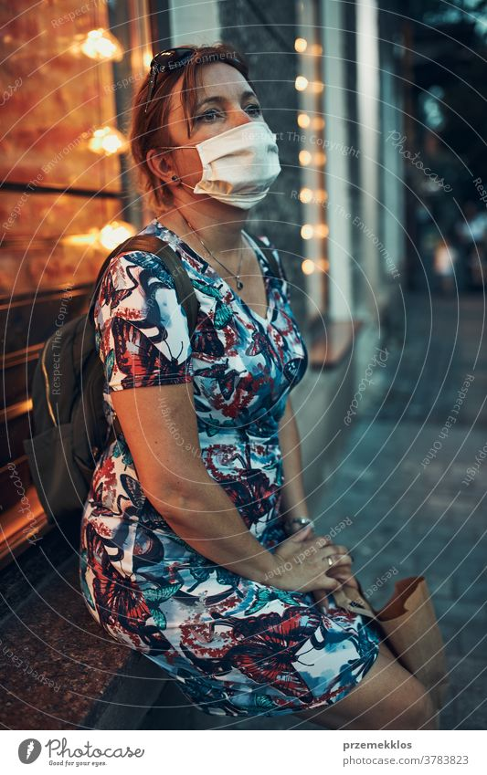 Young woman sitting outdoors at coffee shop front after shopping in the city center, wearing the face mask to avoid virus infection caucasian covid-19 lifestyle