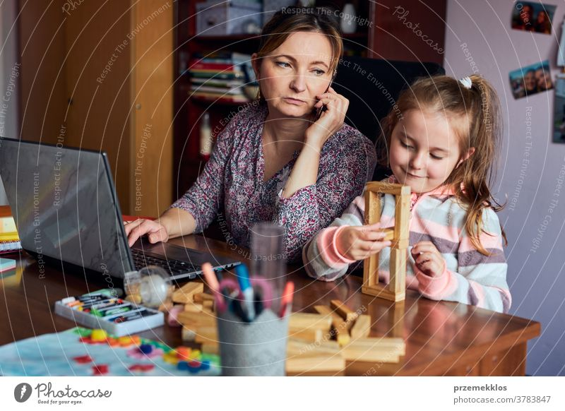Woman mother working doing her job remotely during video chat call stream online course webinar on laptop from home while her daughter playing with bricks toy