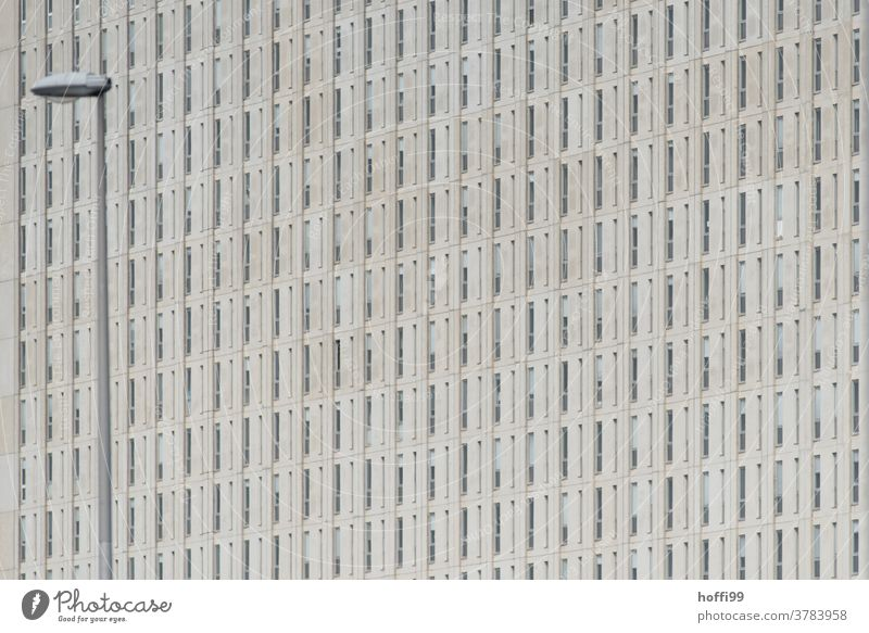 monotonous exterior façade with street lighting Facade Gray dreariness Bleak Venetian blinds Roller shutter Building Structures and shapes Simple Hideous