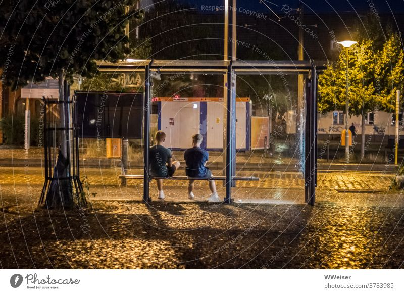 With a friend it's not bad if you have to wait long for the train Stop (public transport) Guys teenager Evening Rain Wet conceit lanterns Street Tram Bus