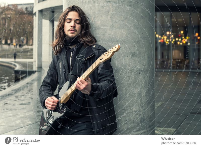 A young musician sings in the government district of Berlin and plucks his guitar Music Musician Guitar Bass guitar Song street music Meditative sad