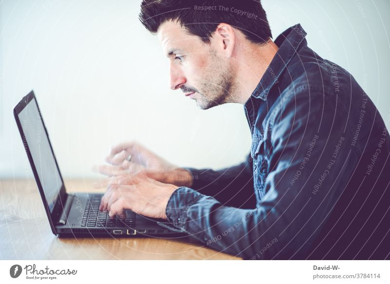 Man types on his laptop with lightning-fast fingers Typing swift Speed concentrated labour Desk home office frantic time pressure Success