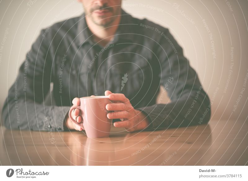 Man holds a cup in his hand and sits at the table Sit Wait Table Cup Coffee Mug hands conversation Drinking