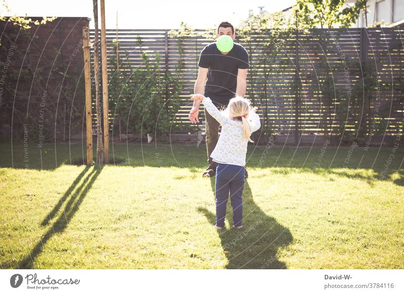 Father and child play together with the ball Child Playing Ball Garden at the same time Together Spring Summer Time Family time in common Daughter
