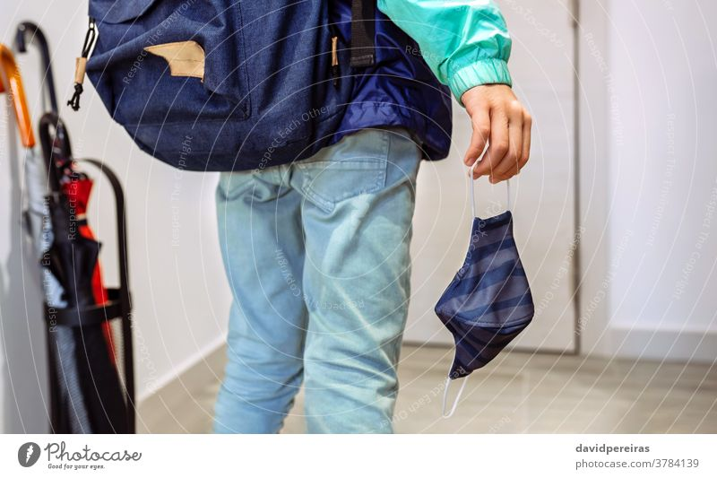Unrecognizable boy with backpack holding mask in hand unrecognizable coronavirus go to school covid-19 child psychological effects epidemic