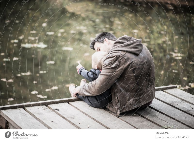 Father and child sitting together on a jetty by the lake Child Nature Footbridge Lake Sit in common at the same time Parents Love Explain Indicate Autumn
