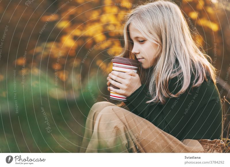 A beautiful teenage girl with blond hair sits thoughtfully in an autumn park, holds a thermos with tea and warms her hands. sad pensive child blonde yellow leaf