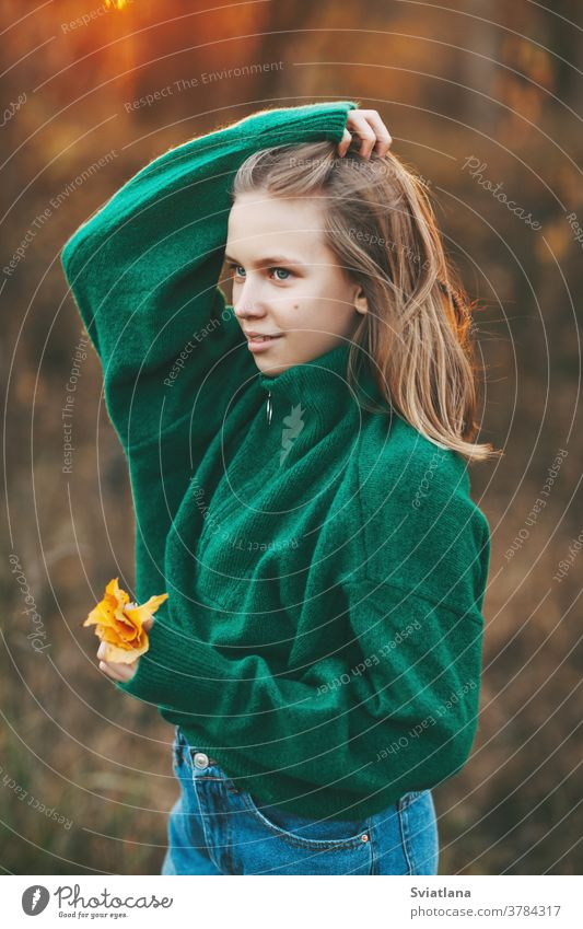 Portrait of a beautiful teenage girl with blond hair and blue eyes with a smile on her face and an autumn yellow leaf in the park. happy blonde portrait fall