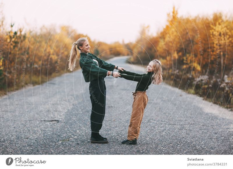 Happy mature mom and her blonde little daughter hugging and laughing while walking in autumn park outdoors woman happy smiling lovely lifestyle kid parent girl