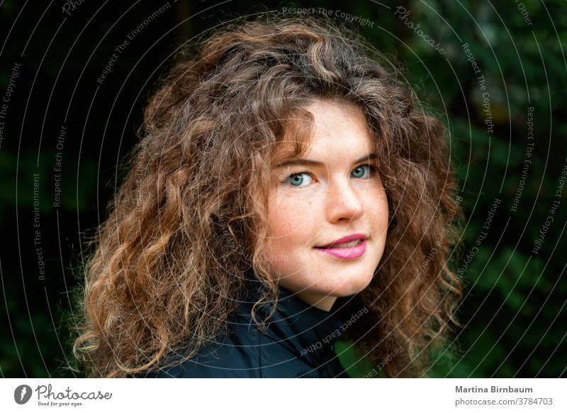 Young natural woman with freckles and wild curly hair looking at the camera young face girl one beautiful caucasian beauty person outdoors hairstyle curls