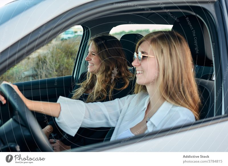 Carefree traveling women in car road trip seaside together friend ride drive summer vacation journey holiday enjoy nature adventure vehicle smile sit cheerful